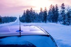 冬天日落和汽车在空的路 库存图片