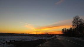 冬天日落和路 免版税库存图片