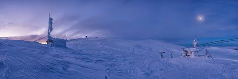 冬天日落在山顶部的雪原在五颜六色的天空下 免版税库存图片