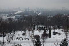 冬天早晨在城市 大厦在雾掩藏在Dnipro的左岸 从公园VÑ-chnoj斯拉维的看法 免版税库存照片