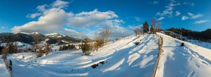 冬天早晨山农村积雪的道路 免版税库存图片