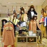冬天时尚时装模特在时尚商店窗口里 免版税库存照片