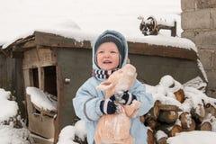 冬天时尚衣裳的两个愉快的孩子乘坐与玩具猪和涉及的一个雪橇河上的桥 第一雪, fam 免版税库存图片