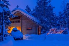 冬天晚上和议院在森林 免版税库存照片