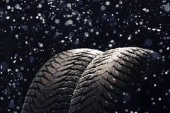 冬天有雪的车胎在黑色 免版税库存图片