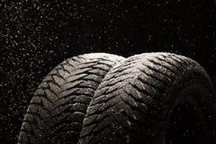 冬天有雪的车胎在黑色 库存照片