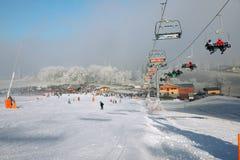 冬天有滑雪倾斜和滑雪吊车的山全景,与雾的晴天和太阳发出光线 库存图片