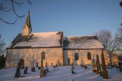 冬天服装和日落的冰山教会 库存图片