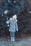 冬天木头的美丽的女孩 女孩在一灰色毛皮大衣打扮 她拿着一个白色圣诞节快乐球 库存照片