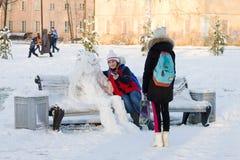 冬天来 做与雪人的两个女孩selfie 免版税库存照片