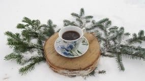 冬天杯子在一个树桩的咖啡构成在雪 图库摄影