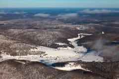 冬天树木繁茂的小山的一点村庄,顶视图 库存照片