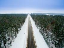 冬天森林和柏油路 在视图之上 照片拍了与寄生虫 杉木和云杉的森林有一条黑路的在 免版税库存照片