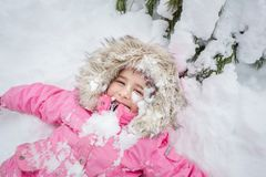 冬天森林女婴的愉快的孩子在雪的一件桃红色夹克的 库存照片