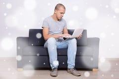 冬天概念-坐沙发和使用膝上型计算机的英俊的人 免版税库存图片