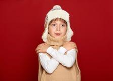 冬天概念-帽子和毛线衣的女孩在红色背景 免版税库存照片