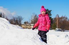 冬天步行的快乐的女孩 免版税库存图片