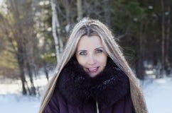 冬天步行的美丽的微笑的妇女 免版税库存图片