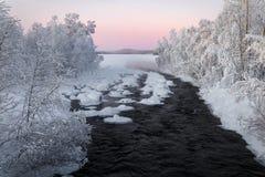 冬天河,包围由树,在芬兰在日落 库存图片
