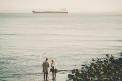 冬天海滩和货船的两个人在距离 免版税库存图片