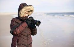 冬天海滩的女性摄影师 免版税库存图片
