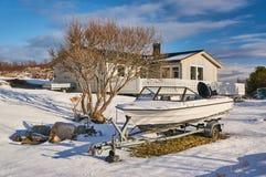 冬天渔村,在房子之间的小船 免版税库存图片