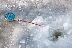 冬天渔的钓鱼竿在冰说谎在孔附近 库存图片