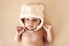 冬天温暖的帽子的逗人喜爱的新出生的婴孩有熊耳朵滑稽说谎的 免版税库存图片