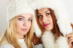 冬天白色成套装备的两个夫人 免版税库存图片