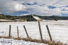 冬天的老木谷仓与篱芭 库存图片