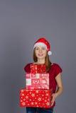 冬天盖帽的微笑的女孩有圣诞节礼物的 免版税库存照片