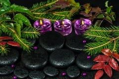 冬天禅宗与下落的玄武岩石头的温泉概念,淡紫色蜡烛 免版税库存图片