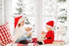 冬天窗口的克里斯愉快的家庭孩子兄弟和姐妹 免版税库存图片