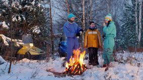 冬天站立在森林的森林家庭在火旁边 溢出在热水瓶杯子的年轻人茶 影视素材
