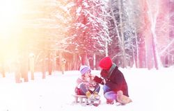 冬天童话、一个年轻母亲和她的女儿乘坐雪撬 库存图片