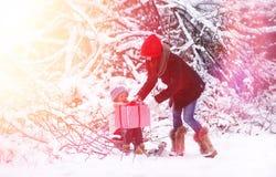 冬天童话、一个年轻母亲和她的女儿乘坐雪撬 免版税库存照片
