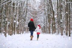 冬天童话、一个年轻母亲和她的女儿乘坐雪撬 免版税库存图片
