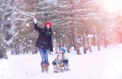 冬天童话、一个年轻母亲和她的女儿乘坐雪撬 图库摄影