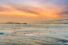 冬天结冰的水湖有日落天空背景 免版税库存照片