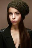 冬天编织帽子和卡其色的夹克的美丽的女孩 与柔和的构成和色的箭头的年轻模型 免版税图库摄影