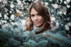 冬天背景witn雪的美丽的妇女 免版税图库摄影