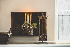 冬天舒适家庭装饰和欢乐假日大气与灼烧的蜡烛、冷杉分支和雪花在壁炉 库存照片