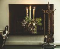 冬天舒适家庭装饰和欢乐大气与灼烧的蜡烛、冷杉分支和雪花在壁炉在客厅 免版税库存照片