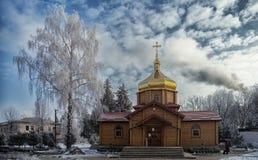 冬天蓝天的背景的木教会 库存图片