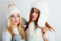 冬天衣物的两个女孩温暖盖帽 图库摄影