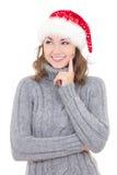冬天衣裳和圣诞老人帽子作梦的微笑的美丽的妇女 免版税图库摄影