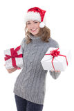 冬天衣裳和圣诞老人帽子的愉快的年轻美丽的妇女与 免版税库存图片