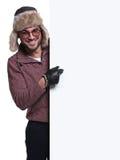 冬天衣裳和裘皮帽的人指向一个空白的委员会 免版税库存图片