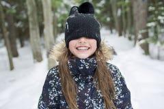 冬天衣裳的女孩 在照片之外的愉快的孩子 免版税库存图片