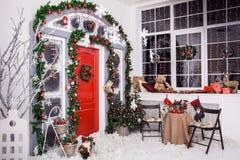 冬天装饰 与圣诞节花圈的红色门 免版税库存照片